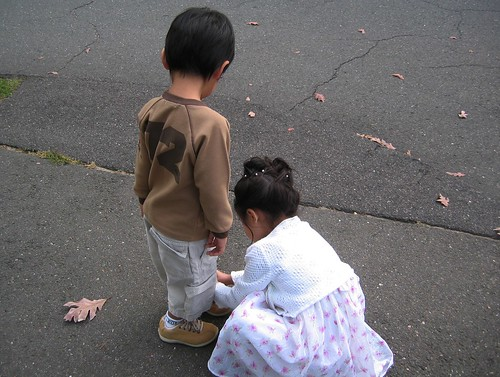 two children: one ties the other's shoelaces