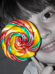 ear(0.0), human body(0.0), dessert(0.0), candy(1.0), confectionery(1.0), yellow(1.0), sweetness(1.0), lollipop(1.0), food(1.0), close-up(1.0), eye(1.0), organ(1.0),
