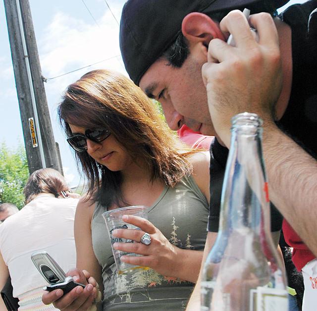 3 people making cell phone calls simultaneously, Fremont, Seattle, Washington, USA