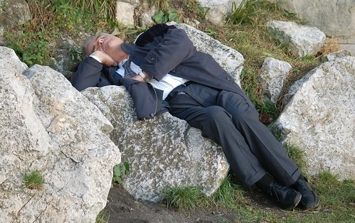 Man in a suit sleeping on rocks