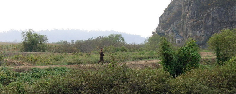 A North Korean soldier strolling along the border line across the streamlet