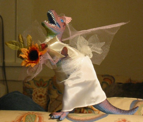 A Godzilla figurine dressed in a white wedding gown