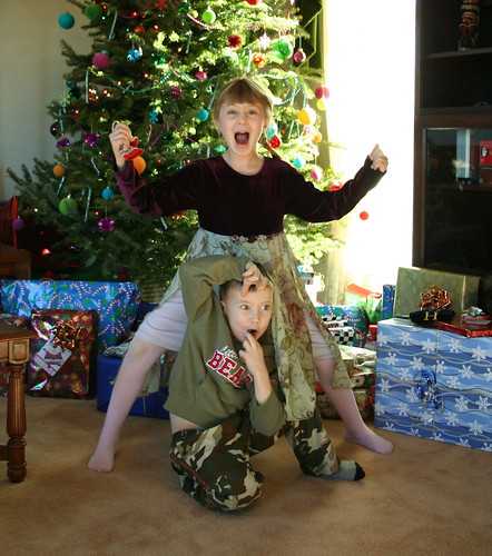 Children by the Christmas tree, make strange faces