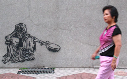 Wall stencil graffiti of a skeletal beggar