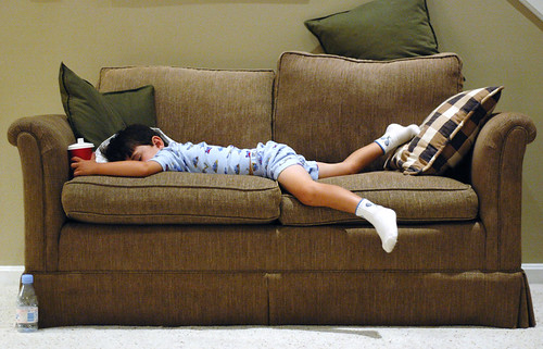 a tan four year old boy wearing tennis socks and bulldozer pajamas asleep on a sofa