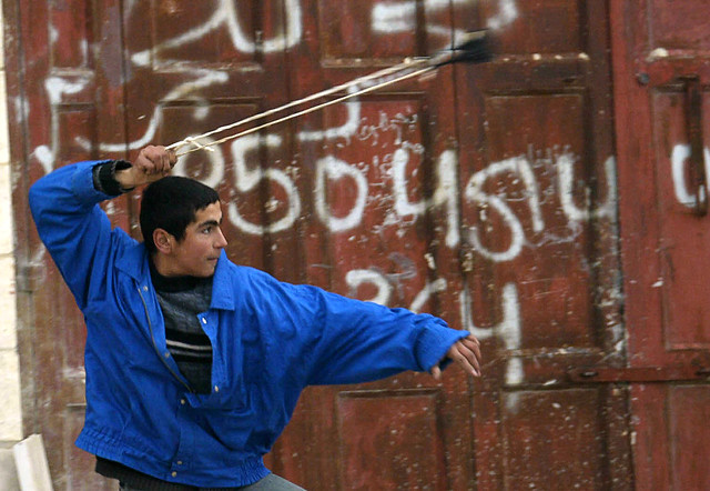 A Palestinian  hurls a stone at Israeli soldiers