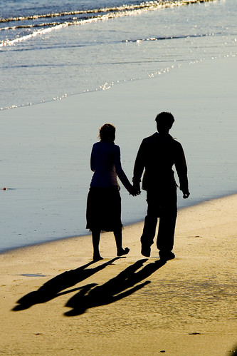 Two people walk holding hands on the beach 2-people-beach-shadows-002