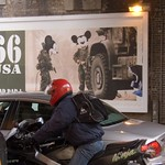 Kawasaki Ninja rider, with Magic Kingdom billboard by James Cauty, in Shoreditch
