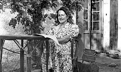 Vintage B&W. August 1938. Charente (France). Lady reading in her garden, in a floral dress.