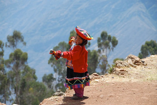 Little girl playing with hand puppets on 4000 m altitude  in Peru