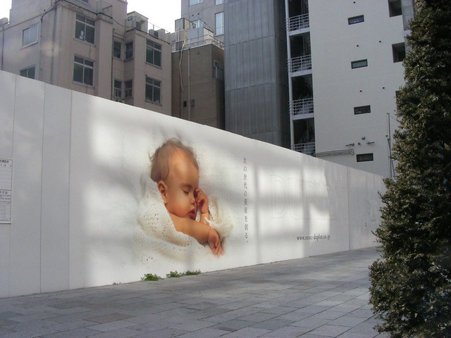 Sleeping baby on hoarding