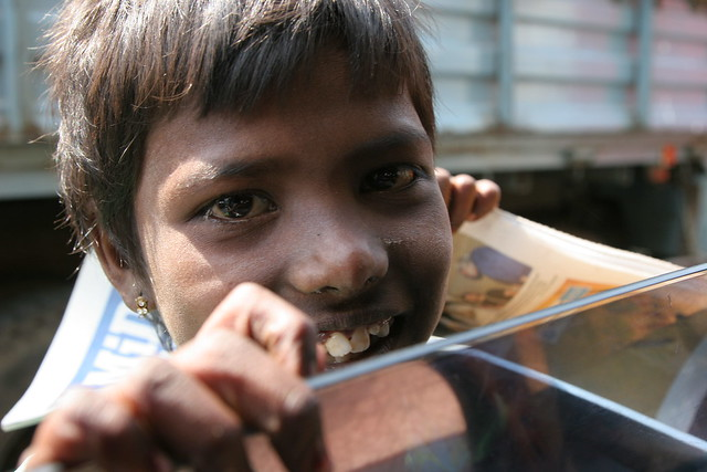 Child sells newspapers in India