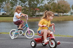baby carriage(0.0), child(1.0), vehicle(1.0), play(1.0), training wheels(1.0), toddler(1.0), bicycle(1.0), tricycle(1.0),