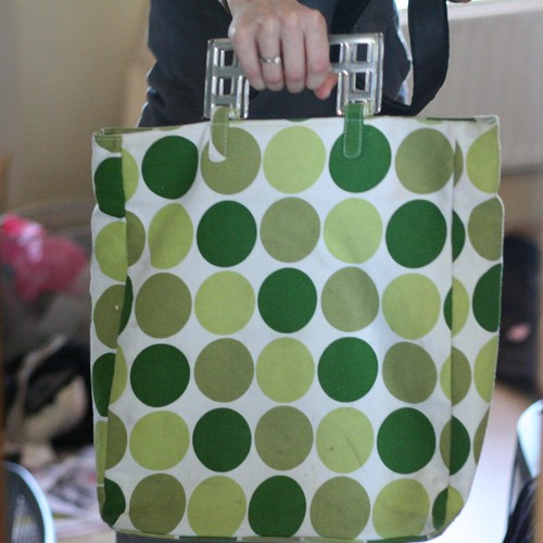 A white shopping bag with green polka dots