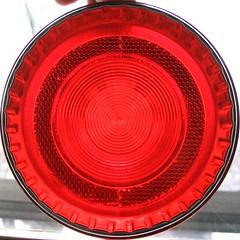 automotive exterior(0.0), wheel(0.0), rim(0.0), font(0.0), grille(0.0), city car(0.0), alloy wheel(0.0), bumper(0.0), lighting(0.0), spoke(0.0), automotive tail & brake light(1.0), automotive lighting(1.0), red(1.0), light(1.0), circle(1.0),