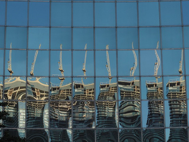 Crane reflected multiple times in glass building