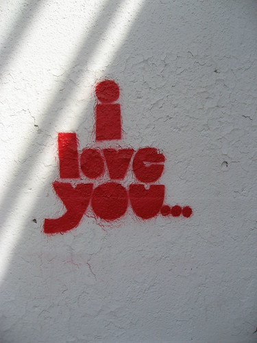 "On a stark, white concrete wall, the words ""I love you"" followed by an ellipses have been spray painted in bright, red spray paint."