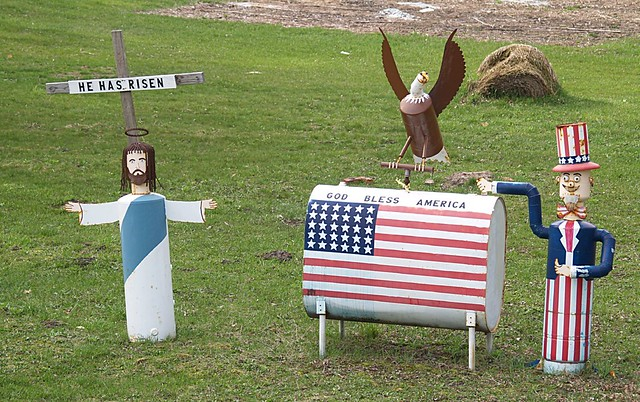 """He Has Risen"" & ""God Bless America"" Lawn Ornaments, On Route 31 (Just North Of Beulah, MI) from Flickr via Wylio"