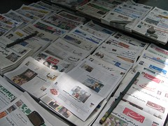 Dozens of Iranian newspapers laid out in rows on the ground for sale