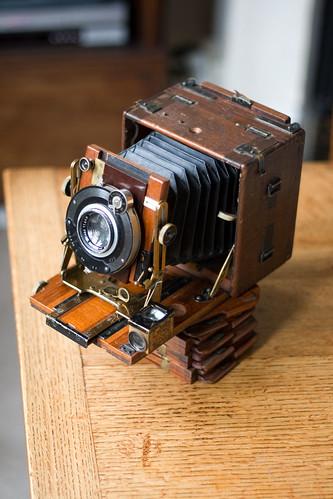 Фото Антикварный фотоаппарат Sanderson с выдвигающимся объективом стоит на столе, картинка Антикварный фотоаппарат