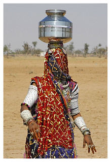 Young bride carrying water