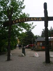 Entrado en Christiania (Copenhague), uno se encuentra este letrero. El barrio libre. Tres círculos amarillos sobre una bandera roja.