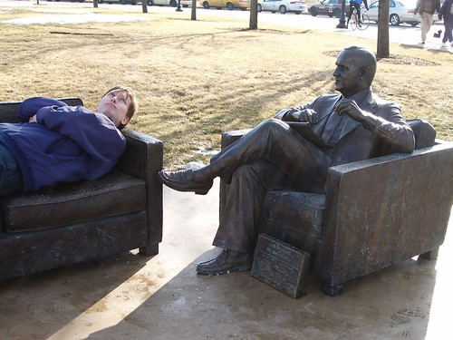 Person lying on couch, talking with Bob Newhart statue.