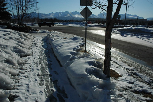 Breakup, sidewalk footprints in the ice and melting snow, pickup truck, signs, Chugach Range, Anchorage, Alaska by Wonderlane