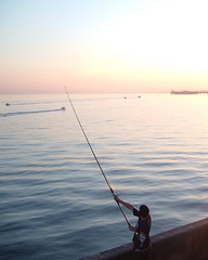 shore(0.0), paddle(0.0), fishing(1.0), sea(1.0), ocean(1.0), surf fishing(1.0), fisherman(1.0), sunset(1.0),