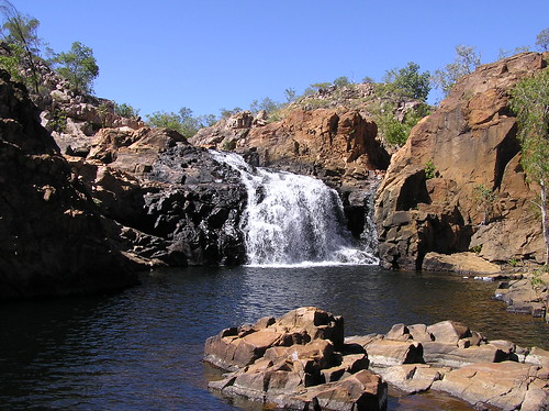 A gushing waterfall flowing into a still pool.
