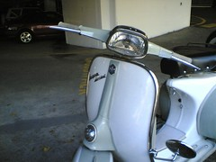 motorcycle(0.0), automotive exterior(1.0), scooter(1.0), moped(1.0), wheel(1.0), vehicle(1.0), bumper(1.0), vespa(1.0),