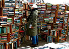 Photograph of a man standing in front of overflowing book shelves in open market