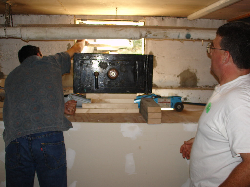 Carl and Barry Moving the Safe Through the Basement Window.