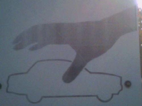 Schwarze Hand klaut weißes Auto