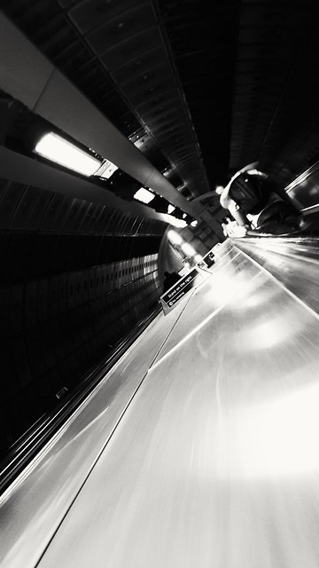 A couple hugs on an escalator of the London tube. They are not in a hurry to catch a train. They are just in the moment.