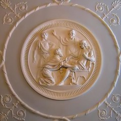 dishware(0.0), platter(0.0), plate(0.0), food(0.0), icing(0.0), porcelain(0.0), carving(1.0), relief(1.0),