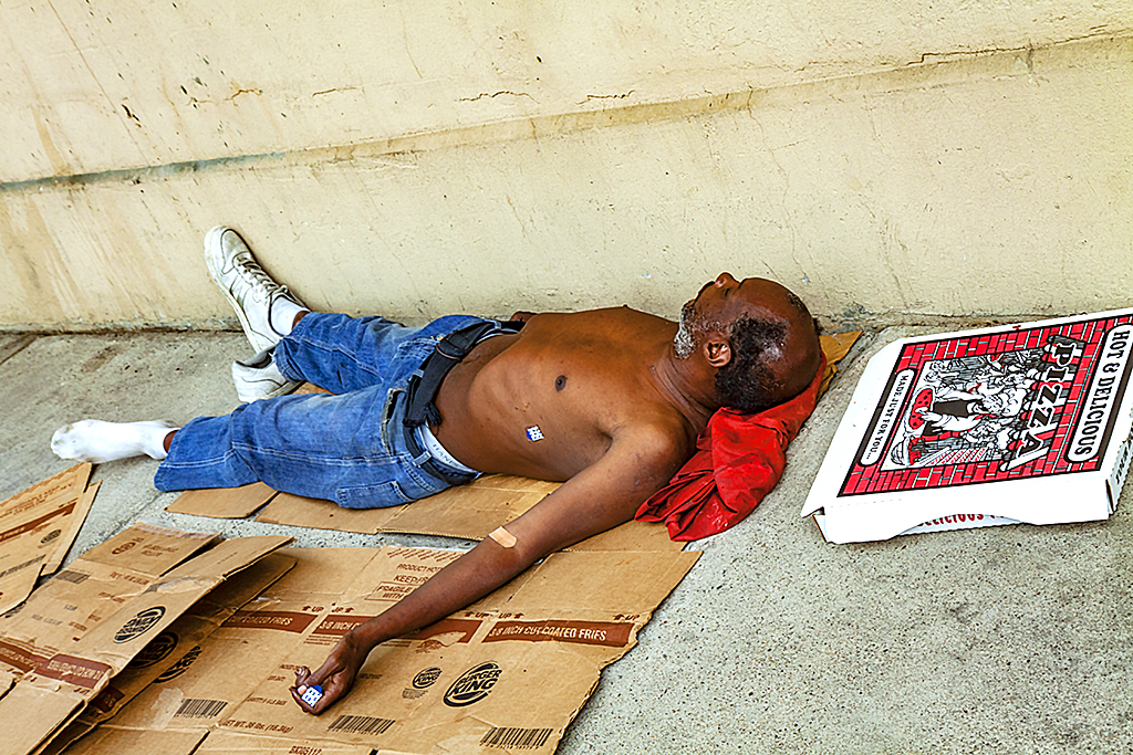 Shirtless man on ground with pizza box--Center City