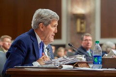 U.S. Secretary of State John Kerry, watched by U.S. Defense Secretary Ash Carter, answers a question on July 29, 2015, as they joined Joint Chiefs of Staff Chairman Martin Dempsey, U.S. Treasury Secretary Jack Lew, and U.S. Energy Secretary Dr. Ernest Moniz in testifying about the Iranian nuclear deal before the Senate Armed Services Committee in Washington, D.C. [State Department photo/ Public Domain]