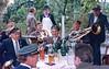 """""""Spritzpause"""" bei einer Hochzeitsfeier in den 80er Jahren. Auf dem Tisch Hochzeitswein und Sodawasser. Für diejenigen mit Blasenschwäche gab es Schnaps in der kleinen Flasche. Die Person mit der weißen Schürze war sozusagen der """"Leibkellner""""."""