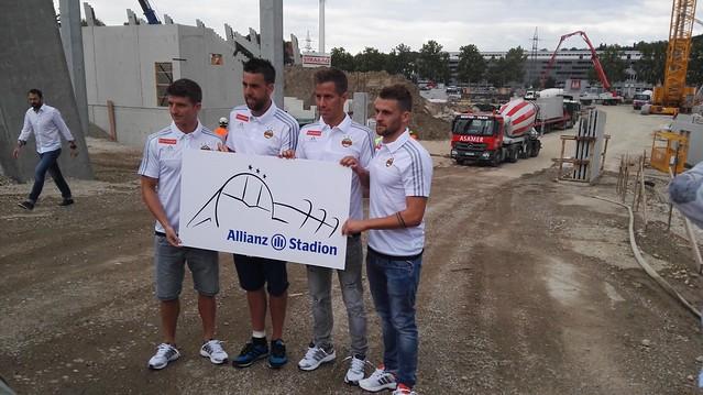 Stephan Auer, Tomi, Stefan Nutz und Philipp Huspek mit dem Logo des Allianz Stadions