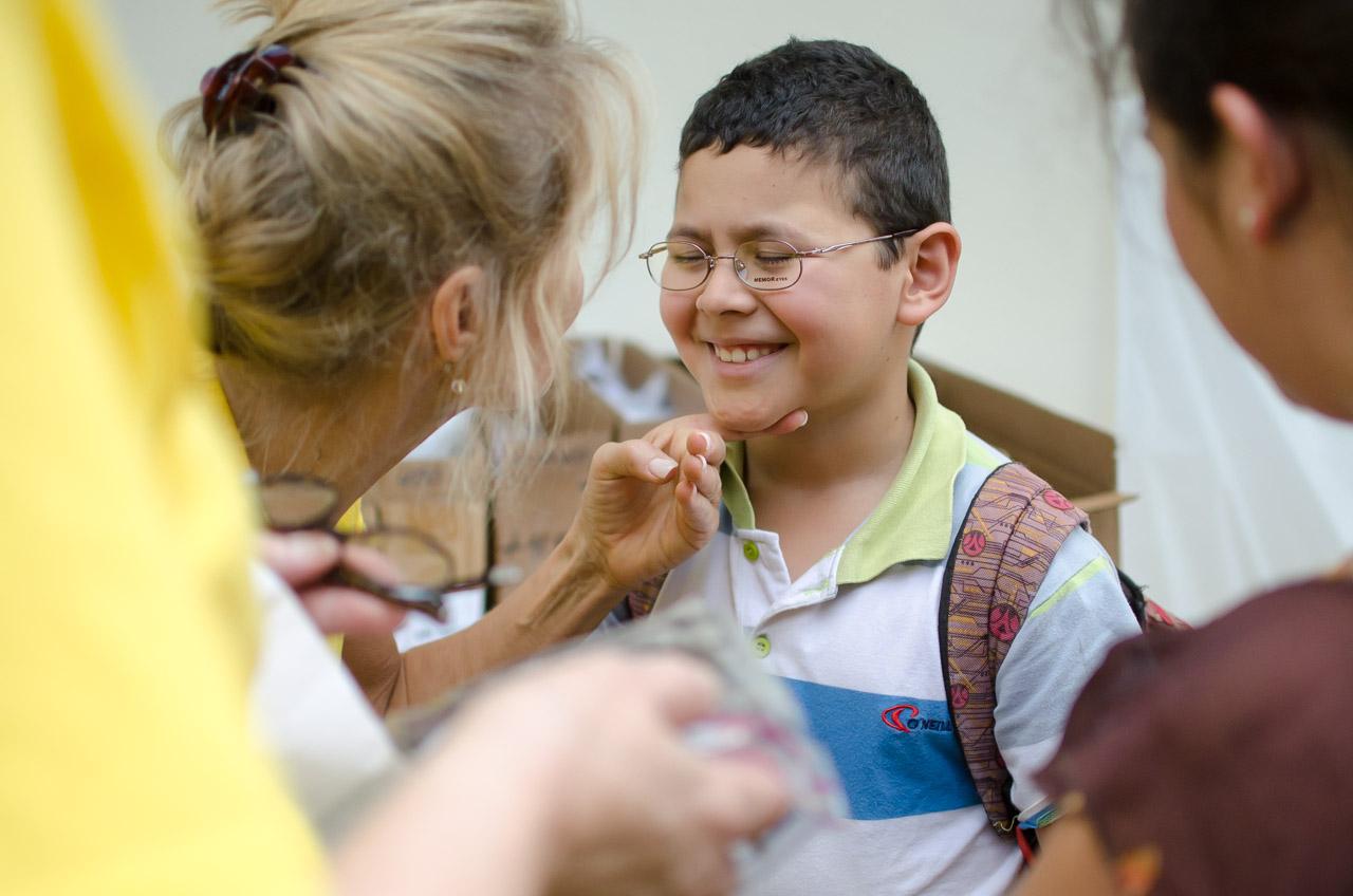 Natalie Venezia, voluntaria de V.O.S.H, intenta convencer a un niño de usar los anteojos que necesita luego de revelarse los resultados de los estudios de su vista. (Elton Núñez)