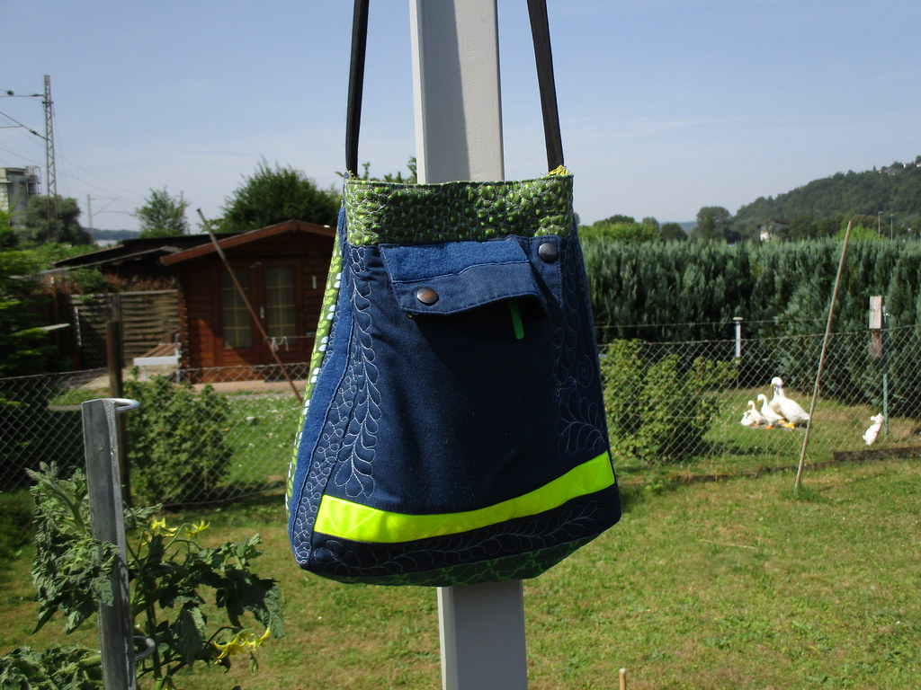 A tote bag made from denim, hung on a fence post. There is a small coop with geese in the background.