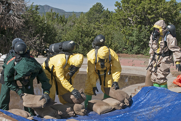 Midwest City, Okla., Fire Department members use sandbags to stop simulated radioactive liquid waste from a spill from flowing downstream during the 2014 Hazmat Challenge.