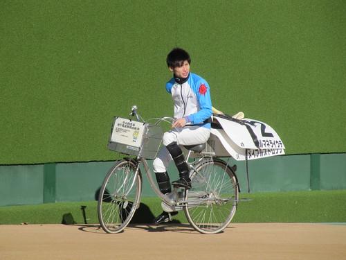 中山競馬場のグランプリロードで自転車に乗る長岡禎仁騎手