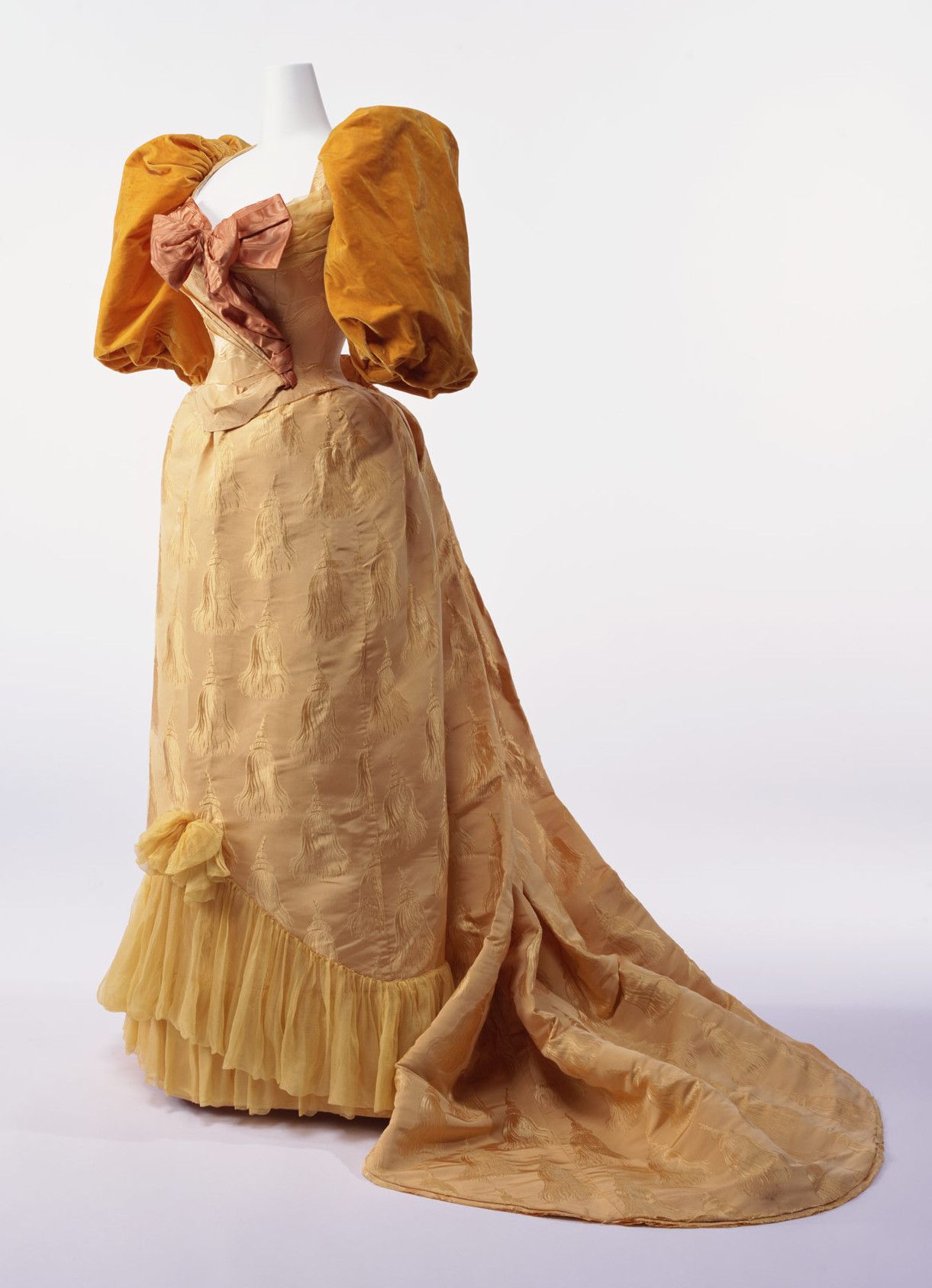 1894. Ball Gown. silk brocade with tassel pattern; two-piece dress with gigot sleeves; silk taffeta bow at breast; silk chiffon decoration at hem of skirt. Credit KCI