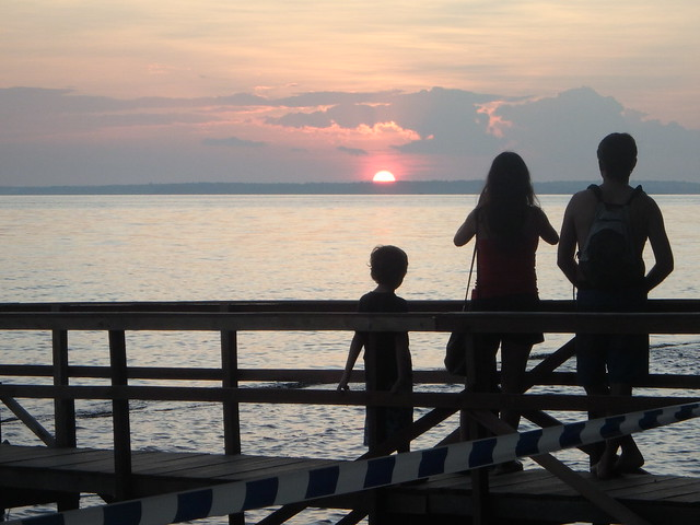 A family watches the sun set over the Rio Negro, Brazil