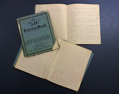 "Three notebooks laid out on a flat dark blue surface.  Two of them are open, showing handwritten pages, and the other is closed, showing a turquoise cover with printing ""The 'J.B.' Exercise Book""."