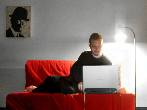 A man sitting on a couch and working at a laptop