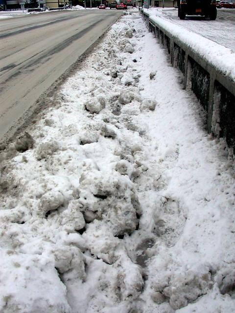 The unfriendly terrain of a wintertime Anchorage sidewalk