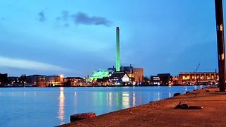 Links: Stadtwerke Flensburg GmbH am Abend. Rechts: Die FSG mbH & Co. KG Werft